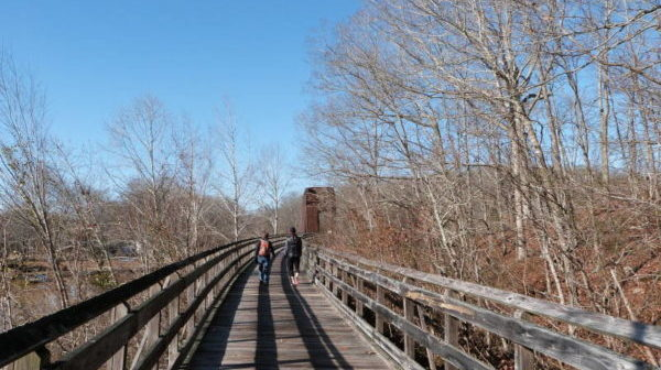 View forward: Two walkers on a boardwalk with converted railroad trestle ahead - among trees and water