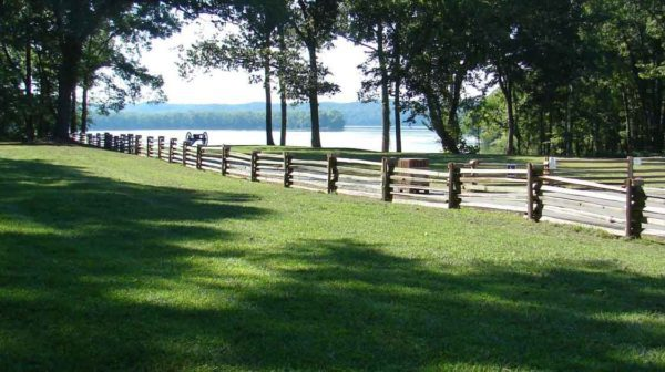 Grassy area with split rail fencing. Civil war cannon and Tennessee River in the distance