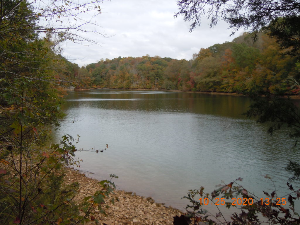 Green lake with rocky shoreline in front and trees covering the far shoreline