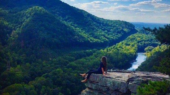 Person on rock ledge high above forest and river with blue sky